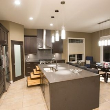 Charcoal maple cabinets and a waterfall quartz island